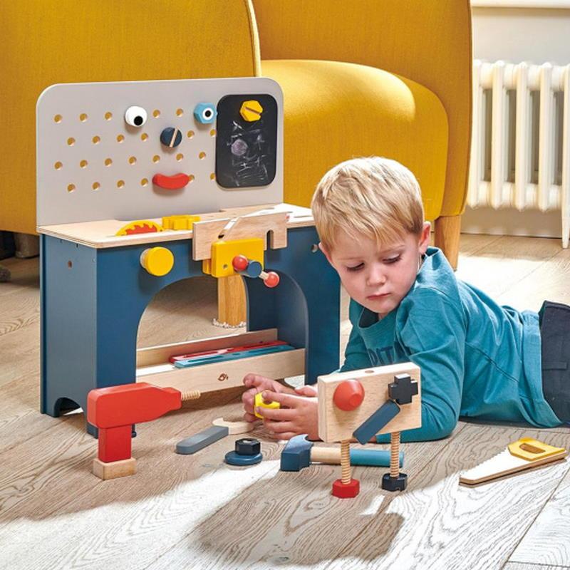 Junge spielt mit Werkbank aus Holz