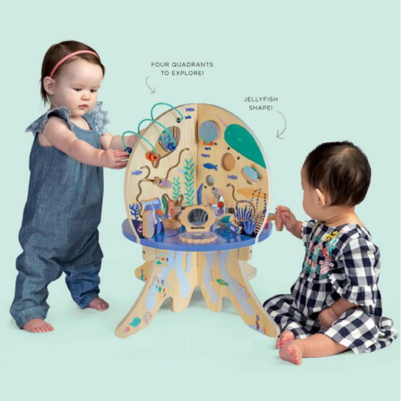 Zwei Kinder spielen am lila Aktivitätstisch