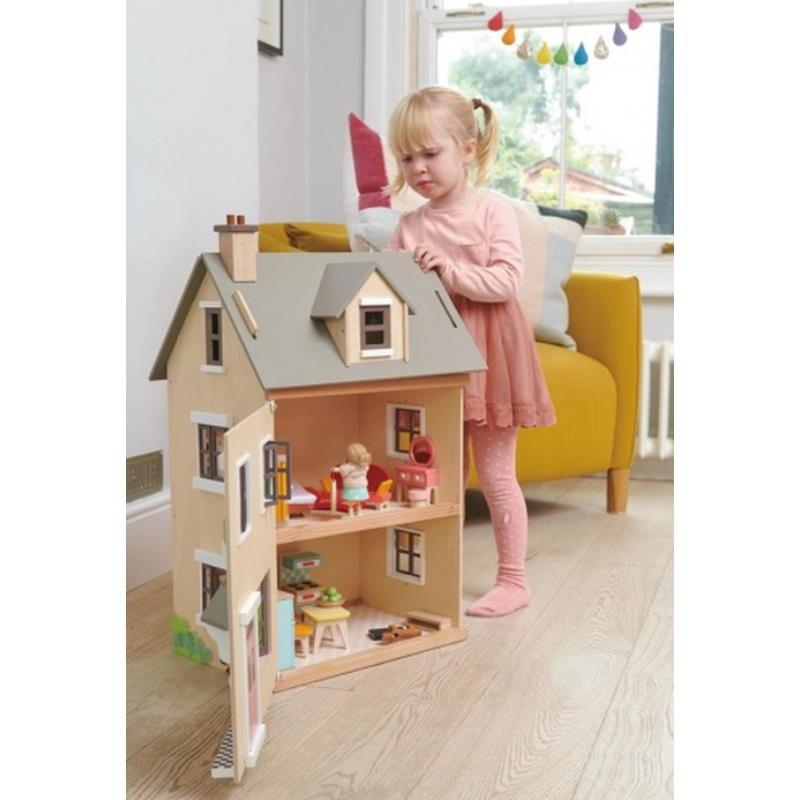 Blondes Mädchen spielt mit einem beschäm Puppenhaus