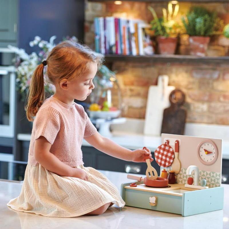 Mädchen spielt mit einer Küchenzeile aus Holz