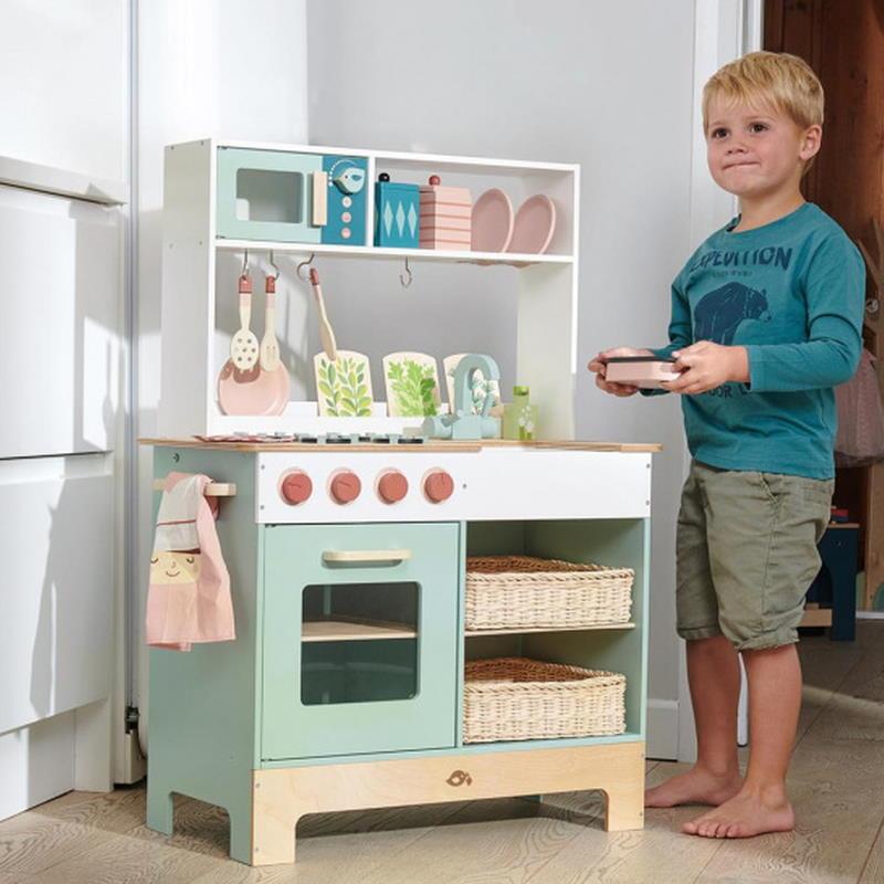 Junge steht neben Spielküche aus Holz in mintgrün