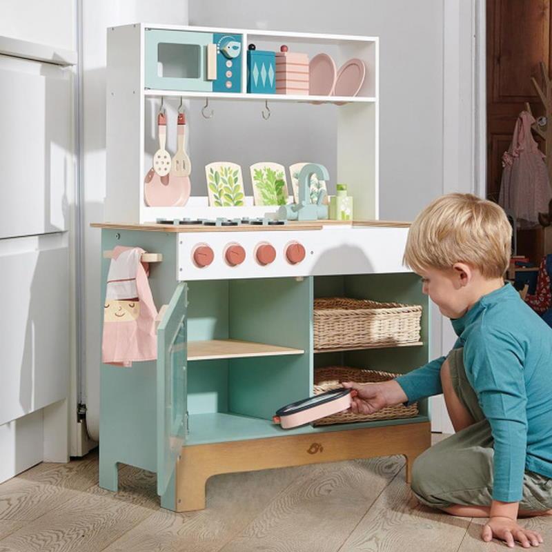 Junge spielt mit Spielküche aus Holz