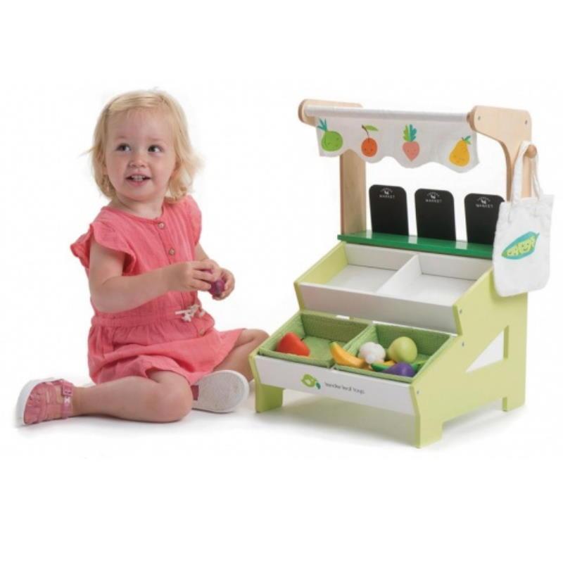 Kind spielt mit Obststand aus Holz