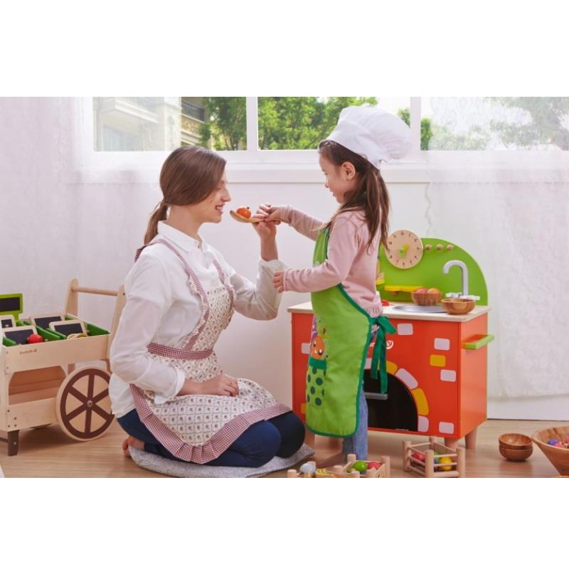 Mutter spielt mit dem Kind an dem Steinoffen aus Holz