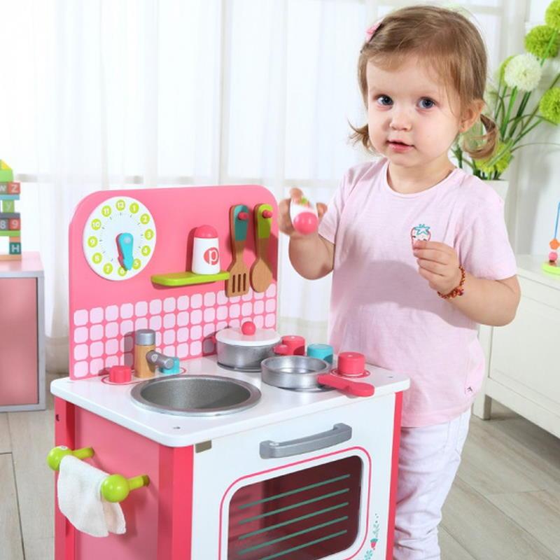 Kind spielt mit einer rosa Kinderküche aus Holz