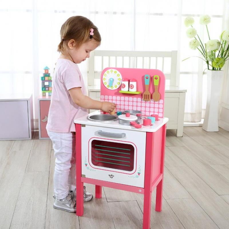 Mädchen spielt mit einer rosa Kinderküche