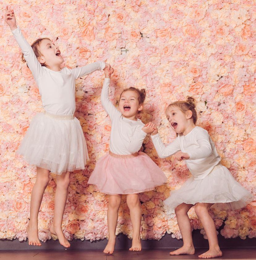 Drei Mädchen springen im mit weisem Oberteil und Röckchen