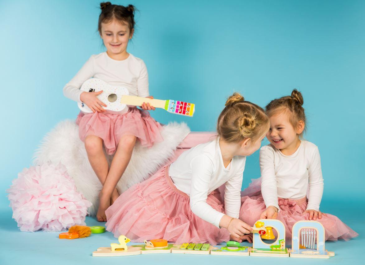 Drei Mädchen, zwei Spielen mit einem Musik Spielzeug und ein auf einer Gitarre